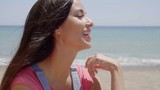 Close up on head and shoulders of happy brown haired lady with ocean beachfront behind her