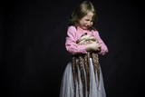 Crying girl in a pink blouse and white skirt on black textured background with octopus hands