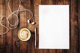 Blank branding template on vintage wooden table background. Blank white letterhead, pen, headphones and coffee cup. Top view.