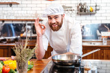 Cheerful bearded chef cook cooking and showing ok sign