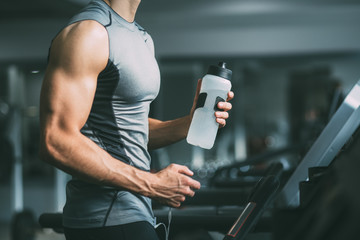 Unrecognizable young man in sportswear running on treadmill at gym and holding bottle of water