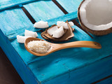 Half coconut with wedges of coconut and shreds on bright blue wooden background. Copy space