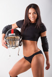 Young woman with football helmet and protection suit on a white background.American Football player girl
