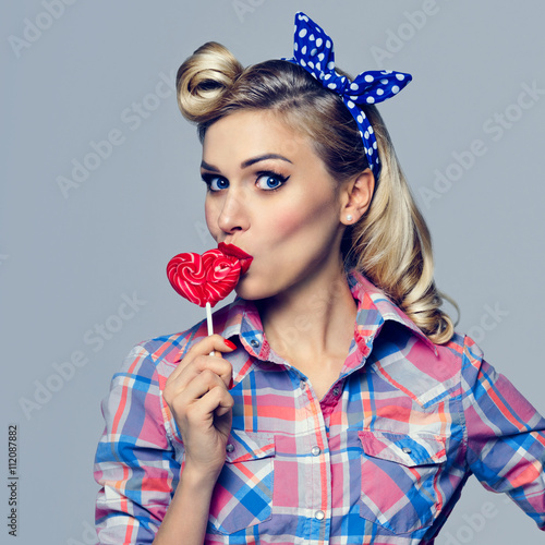 woman eating heart shape lollipop, dressed in pin-up style Poster
