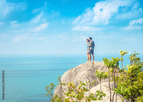 Poster young couple of travelers on a hill with stunning views of the o