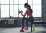 Fitness woman lifting dumbbell in urban loft gym