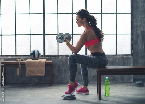 fototapeta na ścianę Fitness woman lifting dumbbell in urban loft gym