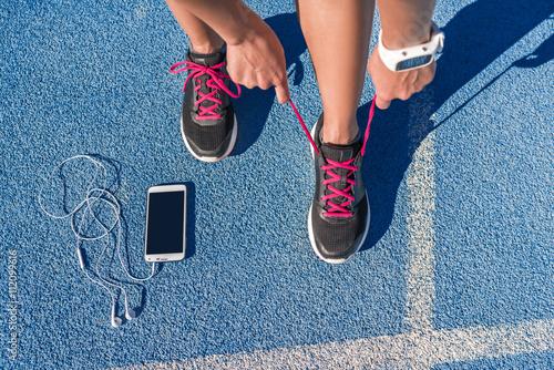 mujer-del-corredor-que-ata-los-cordones-de-los-zapatos-para-correr-preparandose-para-la-carrera-en-la-pista-de-atletismo-con-telefono-inteligente-y-auriculares-para-escuchar-musica-en-el-telefono-movil-atleta-preparandose-para-el-entrenamiento-cardiovascular-pies-en-el-suelo