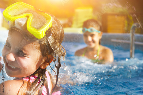 Children playing in pool. Two little girls having fun in the poo