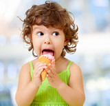 Kid eating ice cream. Funy curly child with icecream on blurred background.