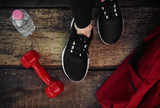 Close-up of woman legs in sportive footwear on wooden floor with dumbbell, bottle and bag. Concept of exercise, fitness and body improvement.