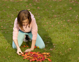 Playing with Autumn Leaves. A young girl is arranging autumn leaves to make a large circle of autumn leaves to imitate a sun because the colours are so bright.