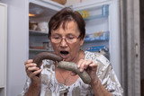 Surprised senior woman holding pork liver sausages