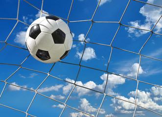 Fußball fliegt ins Tor vor blauem Wolkenhimmel