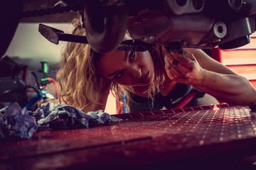 Blond woman repairing motorcycle.