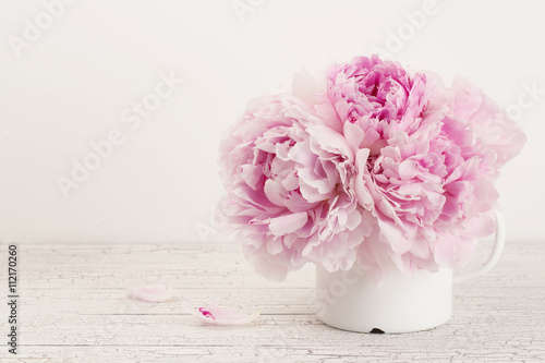 Poster beautiful pink peonies in an enamel mug on a wooden desk, copyspace