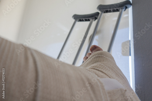 Foto op Aluminium Pedicure Disabled Injured Person With Sprained or Broken Ankle or Foot Sits Inside With Crutches Looking Outside the Sliding Glass Door Window on a Sunny Day.