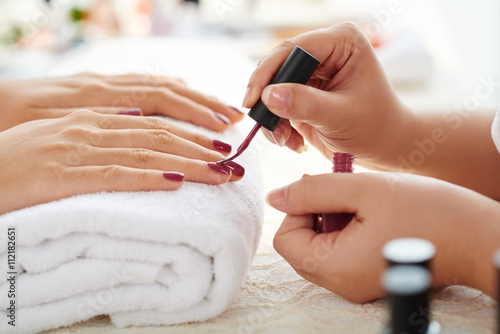 Zdjęcia Side view of manicurist applying marsala nail polish