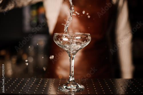 Plagát Barman pouring into champagne glass and making a splash