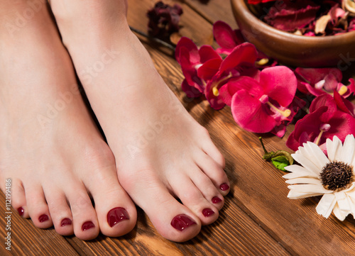 Fotobehang Pedicure Beautiful classic red pedicure on female hand. Close-up.