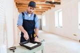 Handyman is preparing paint roller for work