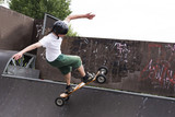 Skateboarder doing a jumping trick at skateboard park with mountainboard.