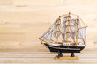 wooden ship model on the table at wood wall background