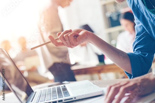 Woman with laptop work process. Startup team at background. Film effect and sun glare effect