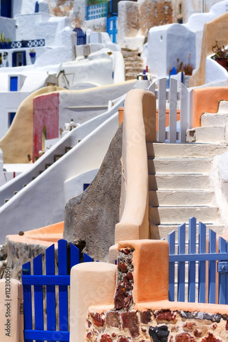 Close up of the narrow streets, small doors and steep stairs of Oia town, Santorini, Greece. Vertical shot