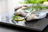 Rainbow trout on a stone board with herbs and lemon