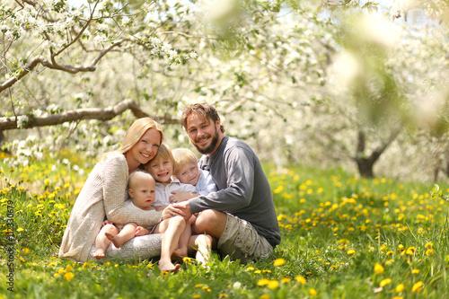 Happy Family of Five Portrait in Spring Flower Meadow
