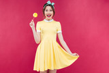 Cheerful cute pinup girl standing and holding yellow lollipop
