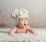 funny little baby in big hat crawling on woolen blanket