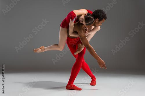 Naklejka Couple of ballet dancers posing over gray background