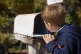 School boy opening a post box and checking mail. Kid waiting for a letter, checking correspondence and looking into the in the metal mailbox.