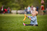Adorable toddler boy with banana sitting on the green grass in the city park and shouting. Child walking in summer park.