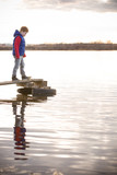 Cute kid boy standing on a wooden bridge and looking at the water in a cloudy spring or autumn day. Child on the river shore. Outdoors. on the pontoon bridge on the river