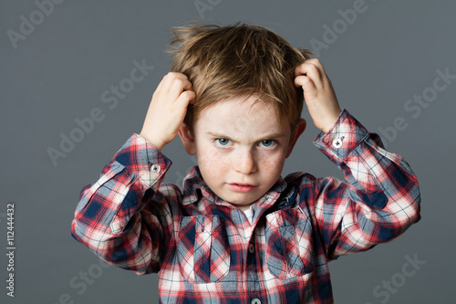 unhappy kid scratching his hair for head lice or allergies