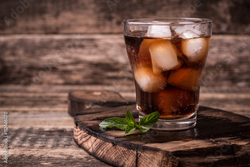 Poster cold drink with ice on wooden vintage table