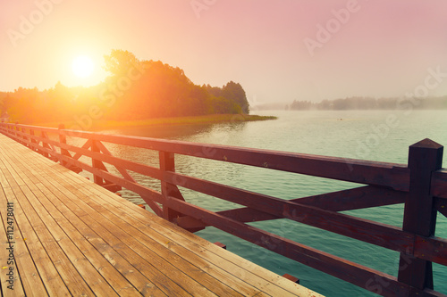 obraz PCV Wooden bridge over lake in early misty morning