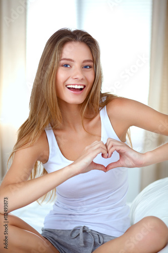Zdjęcia na płótnie, fototapety, obrazy : Beautiful woman showing heart shape on her hand , sitting bed