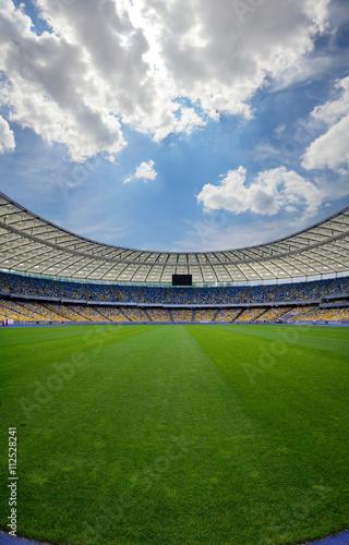 soccer stadium, green grass, blue sky,