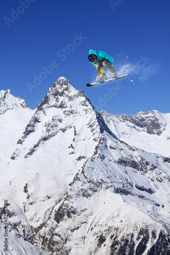 Plagát, Obraz Snowboard rider jumping on mountains