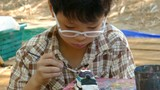 Asian child painting a figurine .
