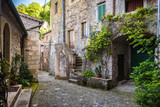 Fototapety Spring streets of the old Tuscan town. Colorful flowers bloom an
