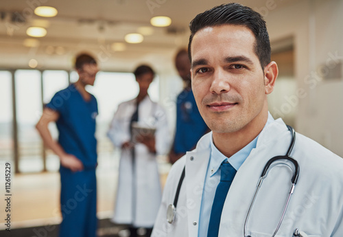 Male doctor with colleagues in background плакат