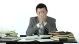 tired student sitting at table studying hard then falling asleep. 4k people stock footage clip at white background.