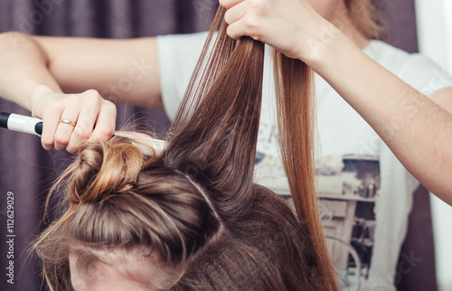 Hairstylist using a curling iron of a female client in a hairdressing salon, clo Poster