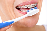 closeup  face of young woman brushing her teeth with a plastic t