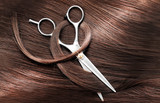 Fototapety Hairdresser's scissors with dark brown hair, close up